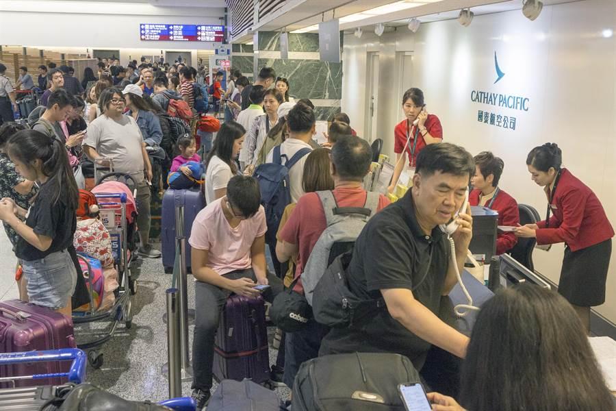 國泰航空地勤人員在接獲總公司通知後,已停止飛往香港的櫃台工作,地勤人員在告知是因為香港機場關場航班全部取消,旅客也只好無奈的開始排隊改票或轉飛澳門或深圳再進香港。(陳麒全攝)