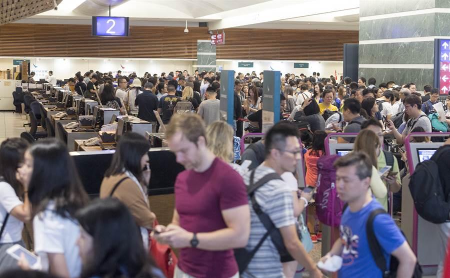 旅客在櫃台前排滿長長的人龍,準備改票或改航班地點再轉進香港。(陳麒全攝)