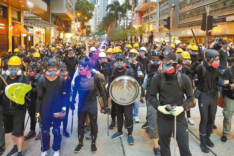 反送中示威者昨戴起防毒面罩,手持盾牌,在港島東和深水埗發起遊行。(美聯社)