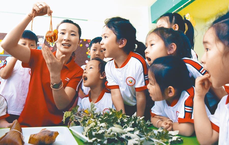 估計2021年大陸幼兒教師和保育員缺口超過300萬人。圖為6月4日,山西幼兒園老師向孩子們介紹香包。(新華社)