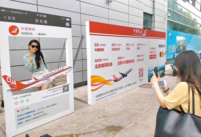 8月9日,旅客在北京南苑機場候機樓外的倒計時牌前留影。(中新社)