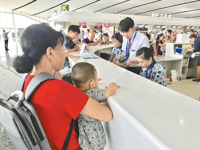 7月19日,北京大興機場舉辦大規模仿真演練,圖為模擬旅客在櫃台購票。(中新社)