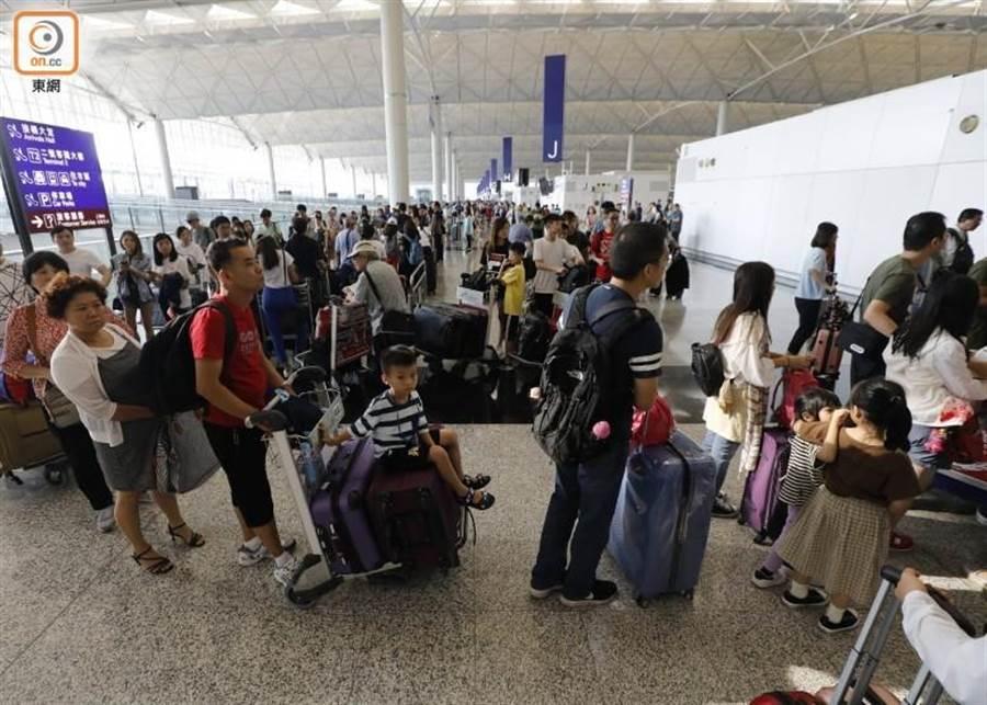 香港機場大批旅客排隊辦理登機手續。(摘自東網)