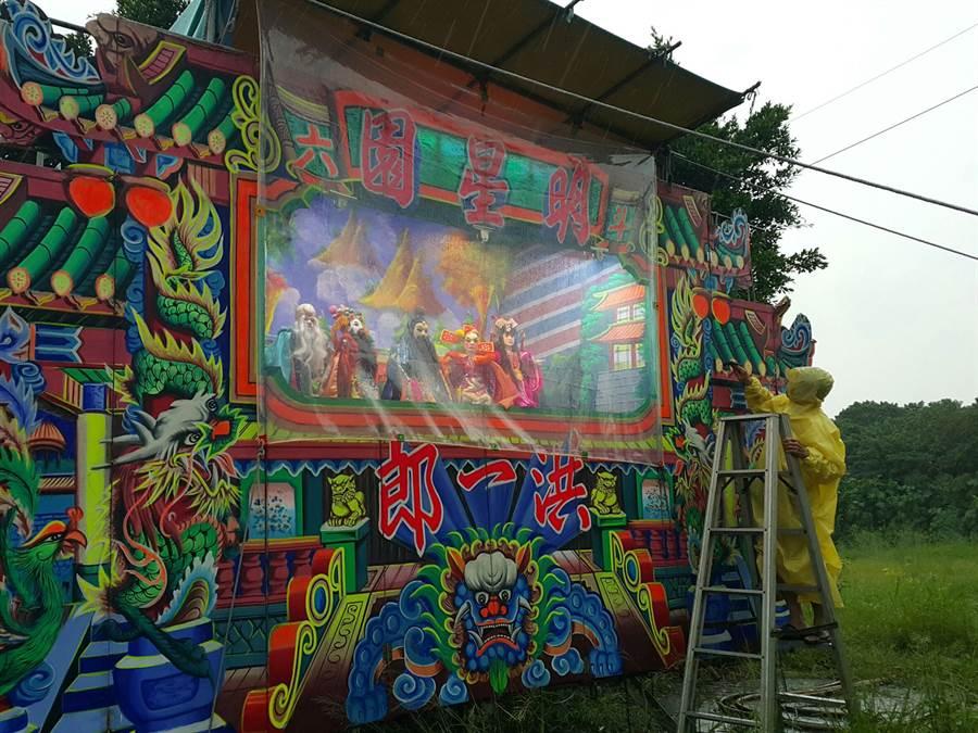 團長洪一郎冒雨拿榔頭把看板釘緊,因戲台上扮仙的布袋戲偶必須演到月底。(周麗蘭攝)