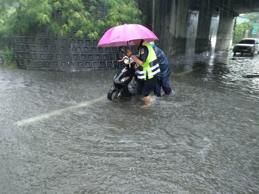 接獲通報的員警趕到積水區,協助阿伯將機車推到路旁安全處。(林欣儀翻攝)