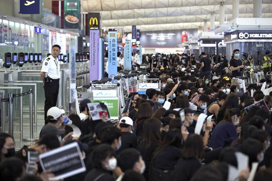 香港機場暫停辦理登機作業5個多小時後,抗議群眾開始陸續轉往第一大樓,枯等數小時的旅客開始辦理登機作業。(圖/美聯社)