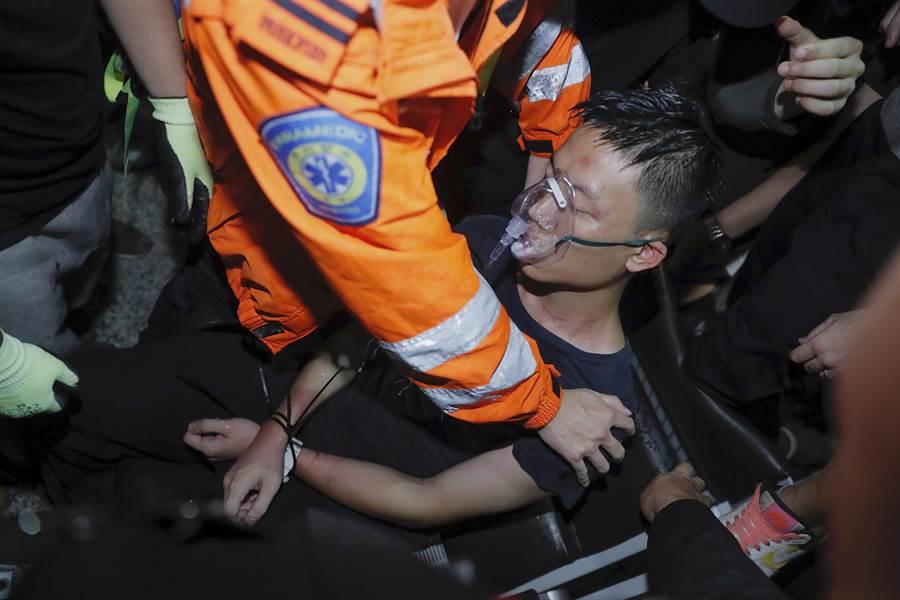 被疑為大陸公安前來臥底的男子被群眾包圍綑綁後,還挨了幾下拳腳,最後由機場救護人員護離開。(圖/美聯社)