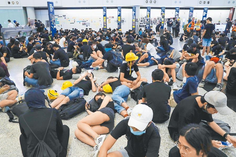 大批示威群眾12日聚集在香港國際機場靜坐,機場管理局宣布,由於機場運作嚴重受阻,已取消所有航班。(美聯社)