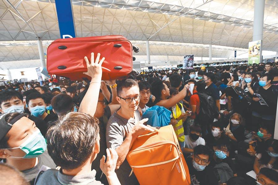 受非法集結影響,航班取消,大批登機旅客受阻。(中新社)