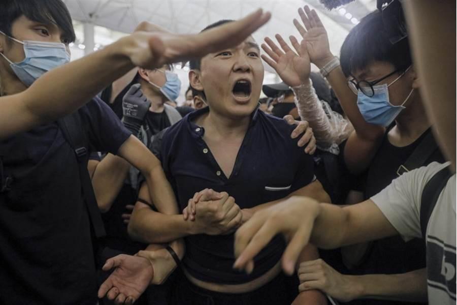 《環球時報》記者付國豪(中)遭香港示威者圍困毆打。(美聯社)