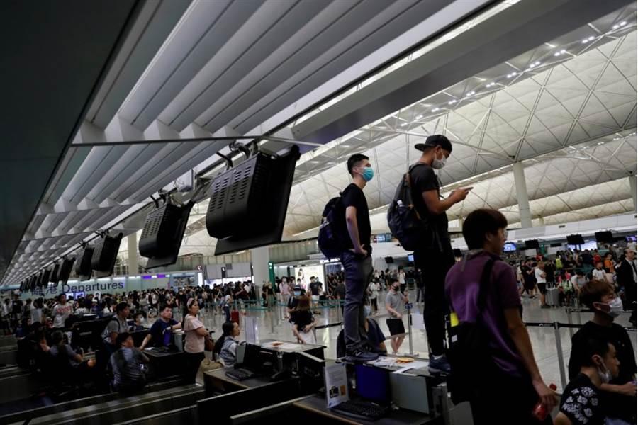 反《逃犯條例》示威者13日晚於機場再次集會,與警方爆發衝突後陸續散去,機場已於今早恢復運作。圖為示威者13日占領機場報到櫃台。(路透社)