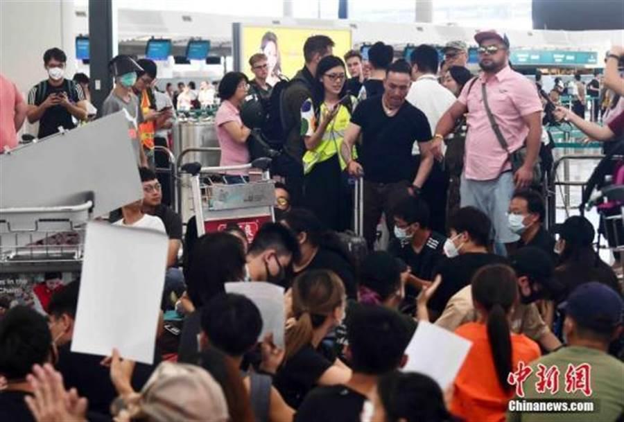 8月13日下午,大批示威者以機場手推車等堵塞香港國際機場1號客運大樓旅客登機行段及保安閘門。(摘自 中新社)