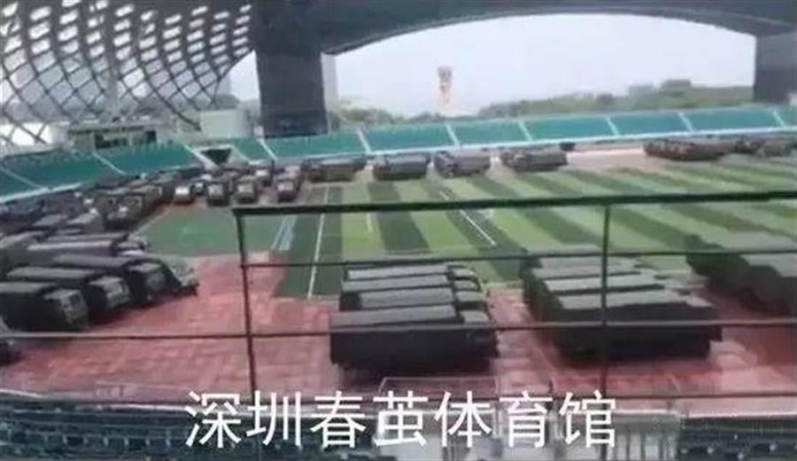 停滿綠色軍車的深圳春繭體育館。(微博截圖)