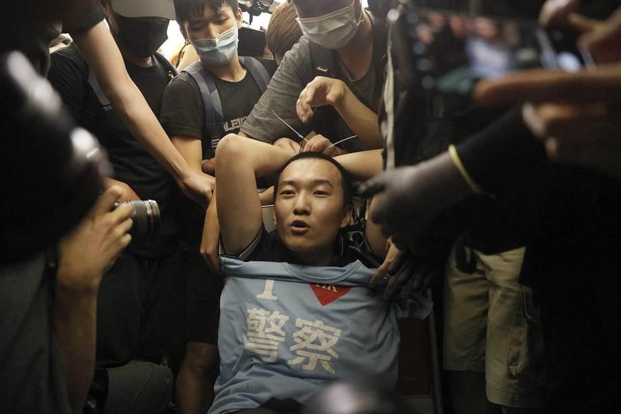 一名持有多種大陸證件的男子被香港機場抗議群眾綑綁,示威群眾懷疑其混入抗議隊伍的動機,這位名男子也遭部份群眾動手毆打。(圖/美聯社)