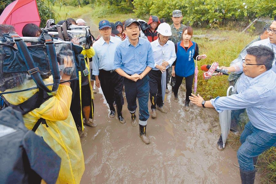 高雄13日凌晨也降豪雨,昨上午主持完防災會議後,市長韓國瑜前往二仁溪沿岸視察水情,因水位超過警戒高度,已實施封橋管制,並疏散居民。(高雄市政府提供)