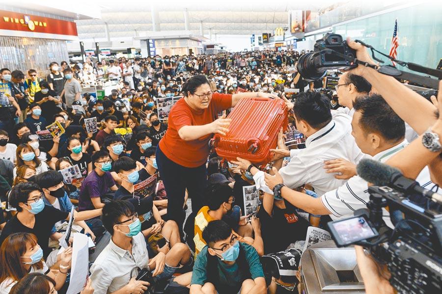 香港機場昨日再度因抗議而停擺,圖為機場內一名旅客走過示威人潮將行李遞給安檢人員。(法新社)