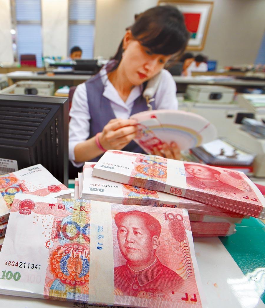 人民幣中間價續破7,創12年新低。圖為銀行行員在辦理人民幣業務。(本報資料照片)