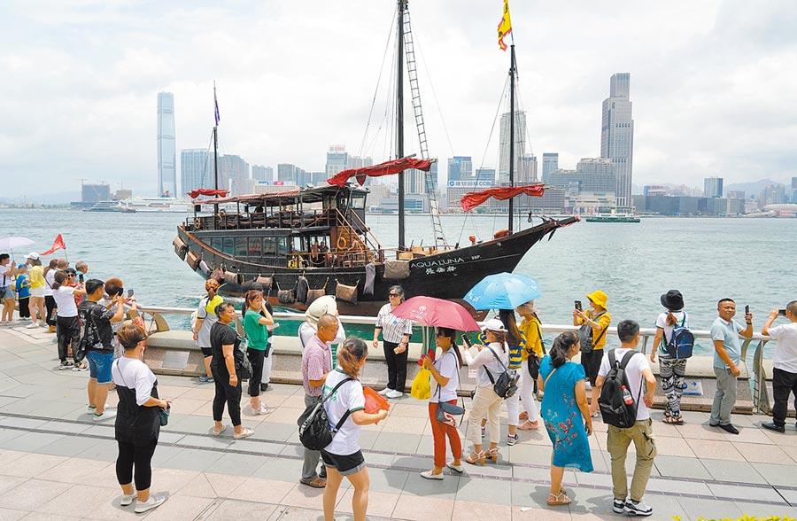 香港示威行動,導致7、8月分旅遊旺季變「寒冬」。圖為7月9日,遊客在金紫荊廣場旁海濱拍照。(中新社)