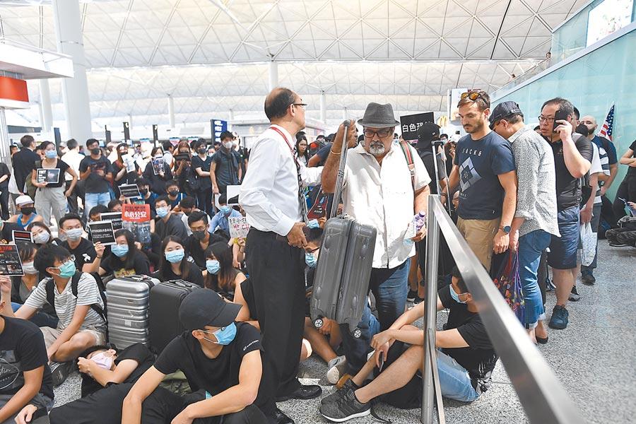 大批黑衣示威者13日下午3時許堵塞香港國際機場南面及北面離港閘口前通道,登機旅客大排長龍。(中新社)