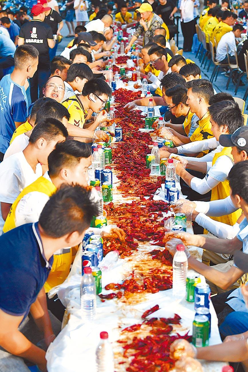 6月30日晚,成都某外賣盒飯店擺上小龍蝦「暖心宴」,邀400餘名外賣員免費品嘗。(中新社)