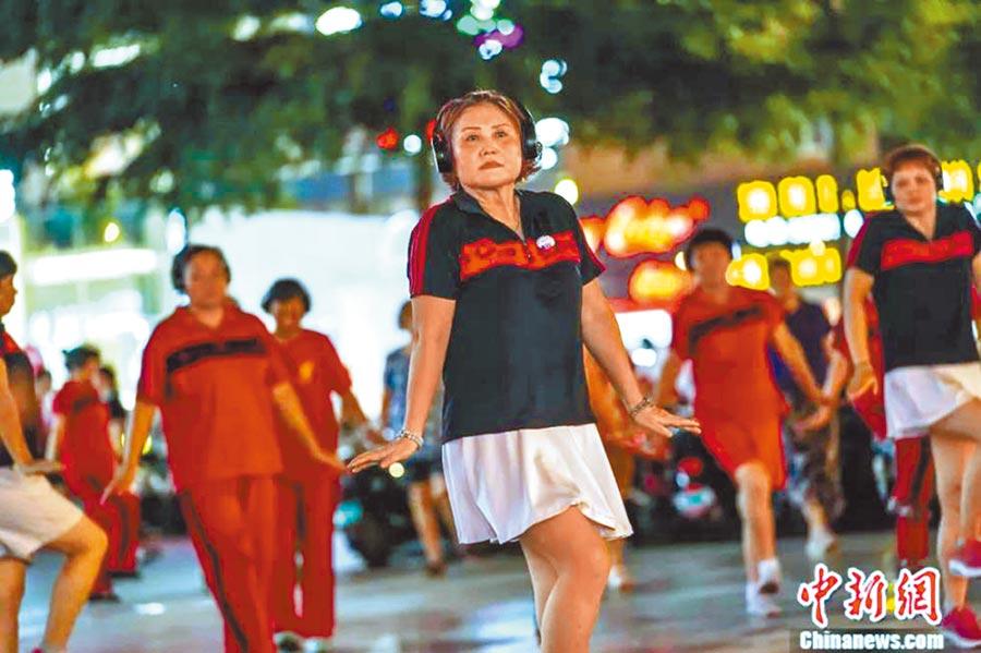 8月9日晚,廣西南寧大媽戴耳機跳「靜音」廣場舞。(取自中新網)