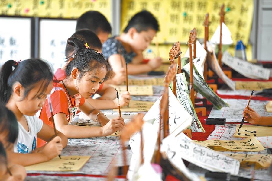 7月20日,安徽省肥西縣紫蓬鎮中心學校開辦暑期興趣班,學生們在練習書法。(新華社)