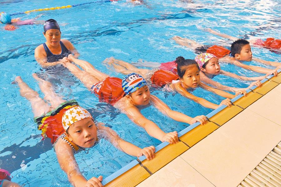 開心泳池度暑期,教練指導小學生們蛙式的要領。(新華社資料照片)
