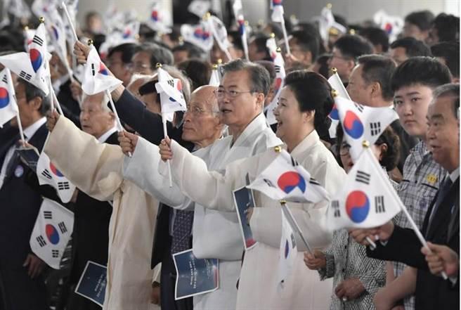 南韓總統文在寅與夫人金正淑今天在南韓光復74週年紀念儀式上揮舞南韓國旗。(路透)
