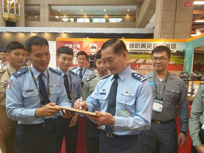 國防工業展參展官兵與沈一鳴合照,並請沈一鳴簽名紀念。呂昭隆攝。