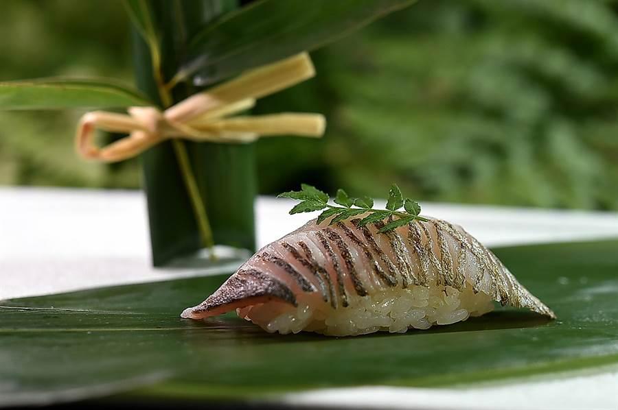 〈粽壽司〉是用粽葉包裹壽司作成的特殊壽司,〈Ukai割烹〉主廚用脂脂豐厚的基隆油帶魚,略醃漬後並炙烤作成壽司再用粽葉包捲,所以風味更富層次。(圖/姚舜)