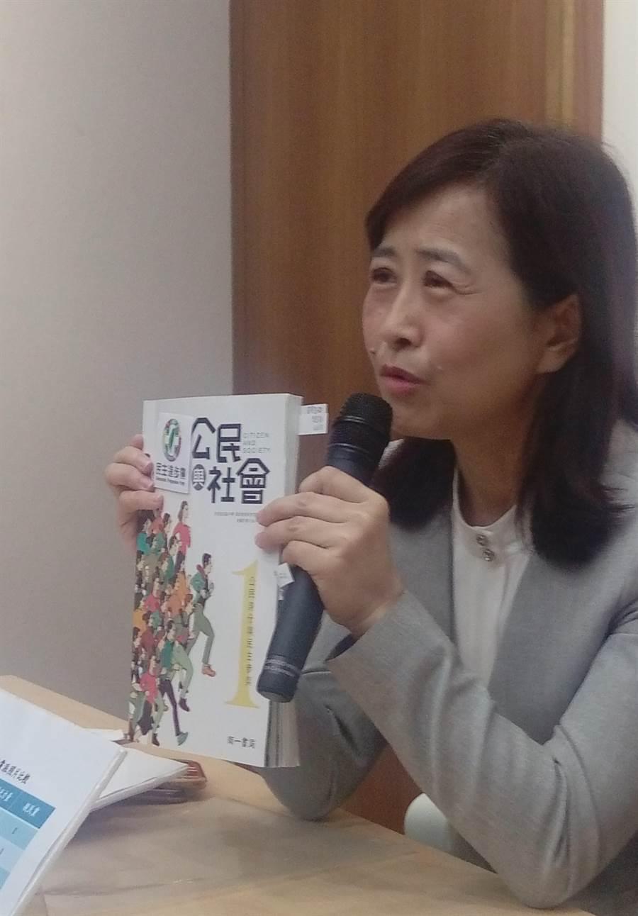 林奕華手上拿著特定版本教科書,質疑該書選圖偏頗(記者季節攝影)