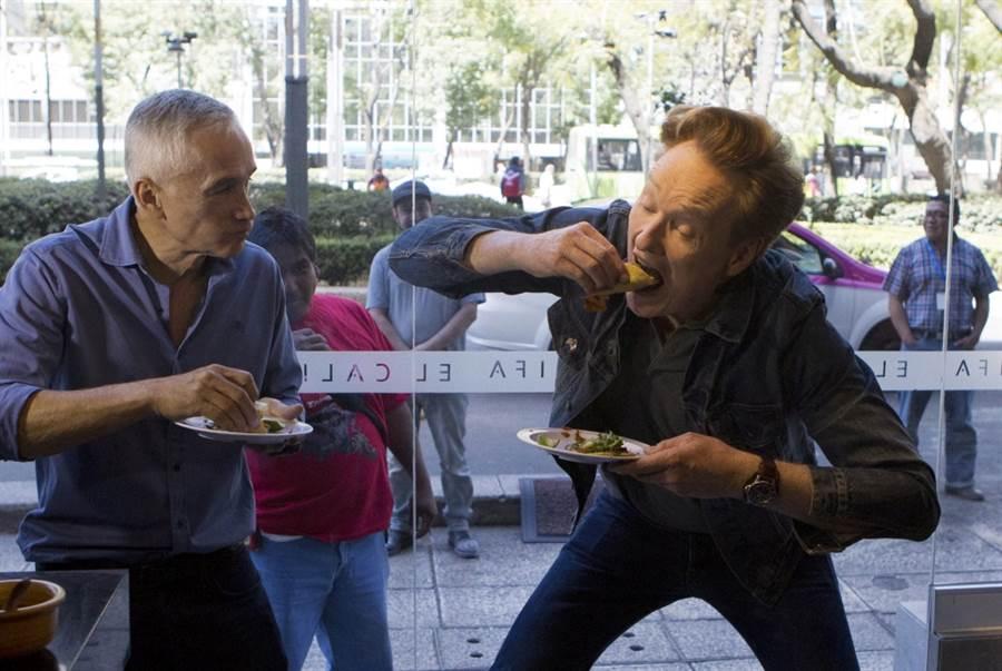 知名脫口秀主持人康納(右)在鏡頭前大口吃夾餅。(美聯社資料照)
