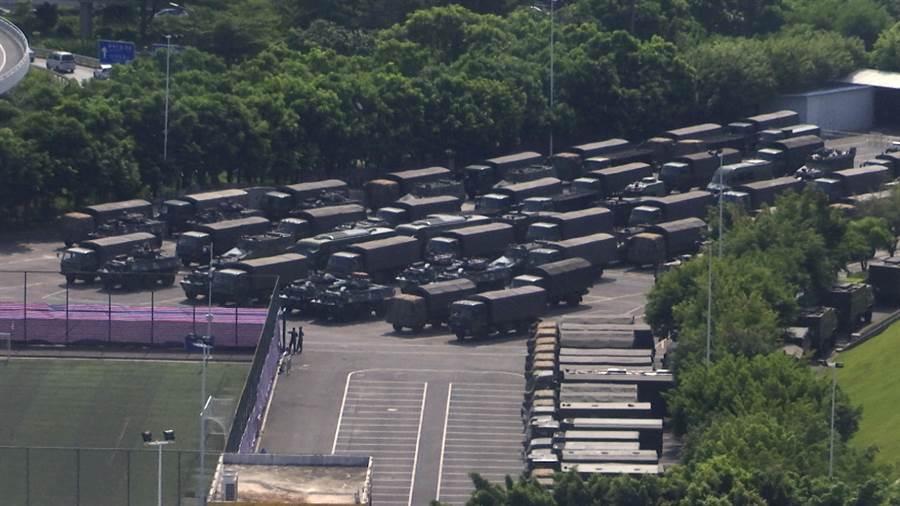 深圳灣體育館外集結大量運送部隊的車輛,外媒甚至猜測以這種規模大約會有一萬名武警在此準備,這種機動化裝備10分鐘就可全部運抵香港。(圖/美聯社)