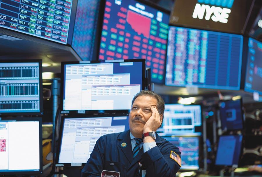 全球股市大地震,美股14日大跌800點,紐約證券交易所交易員在收盤前,神情顯得沮喪。(法新社)