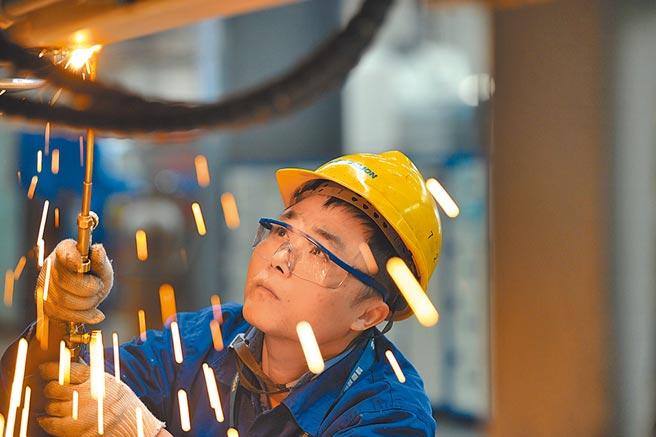 大陸推動企業結構性去槓桿,完善企業債務風險監測預警機制。圖為工人在中聯重科長沙的工廠裝配整車。(新華社資料照片)