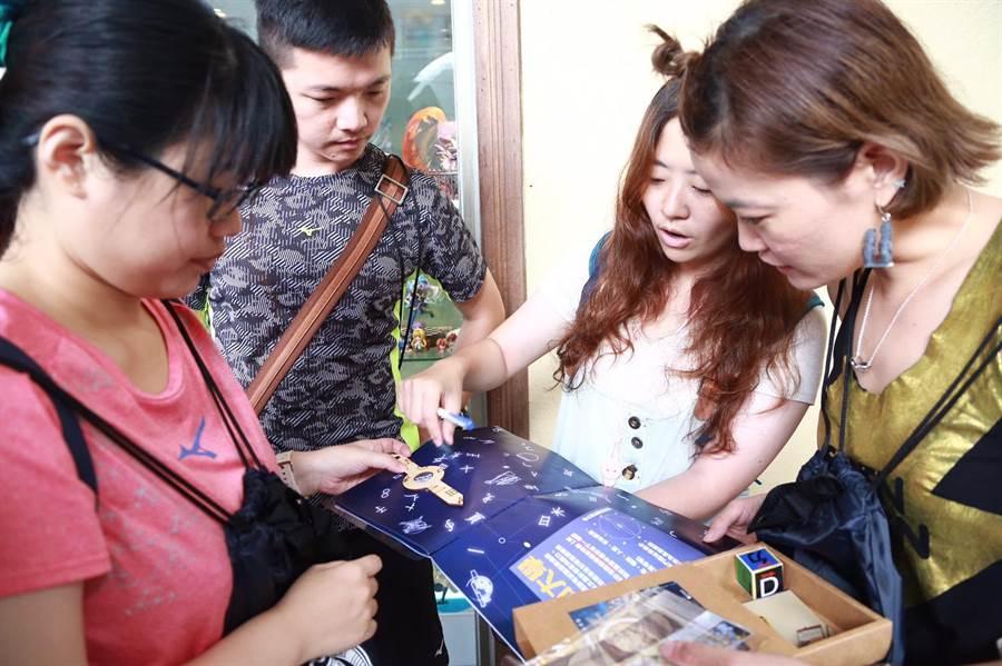 台南市觀旅局繼去年與寶可夢公司配合活動,吸引百萬觀光潮後,今年與在地遊戲公司再推出新款的實境遊戲,報名的玩家看著道具包研究解謎方法。(台南市觀旅局提供)