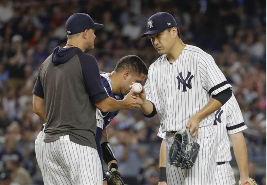洋基先發投手田中將大(右)將球交給總教練。(美聯社)