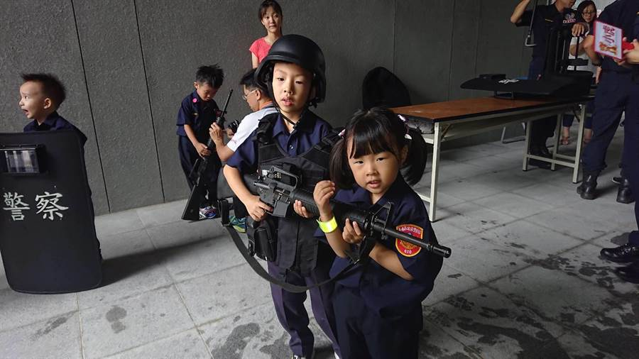 台南市警察局舉辦「小小警察營」預防犯罪宣導活動,幼童穿起警裝,賣力扛起長槍模樣超萌。(程炳璋攝)
