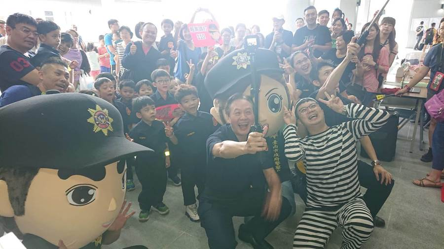 台南市警局長周幼偉(前排中蹲者)與小小警察玩起手機自拍。(程炳璋攝)