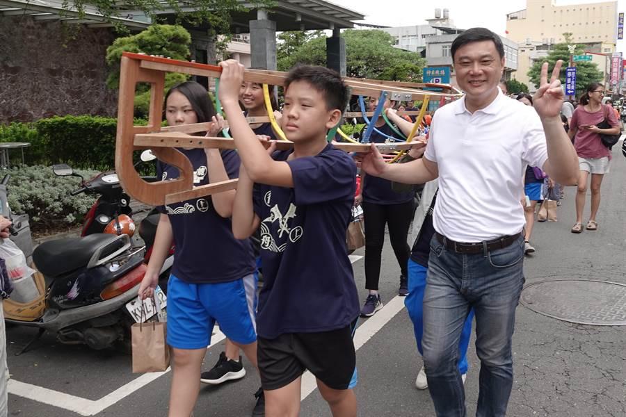 鹿港鎮長許志宏(右)陪著大小朋友們開心踩街遊行。(謝瓊雲翻攝)
