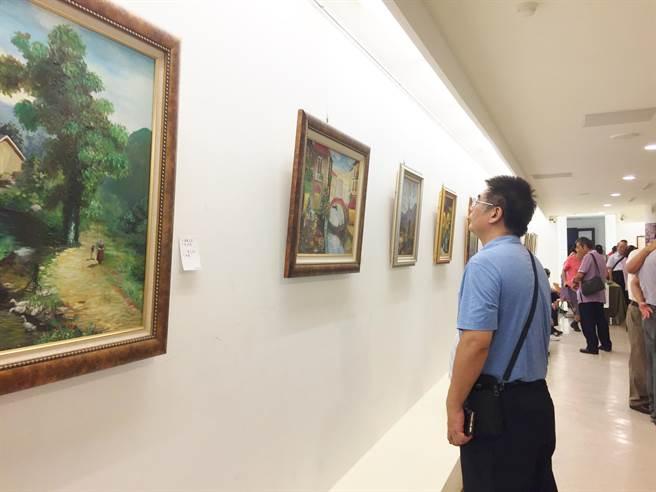 油畫懸掛牆面,民眾專心欣賞。(巫靜婷攝)