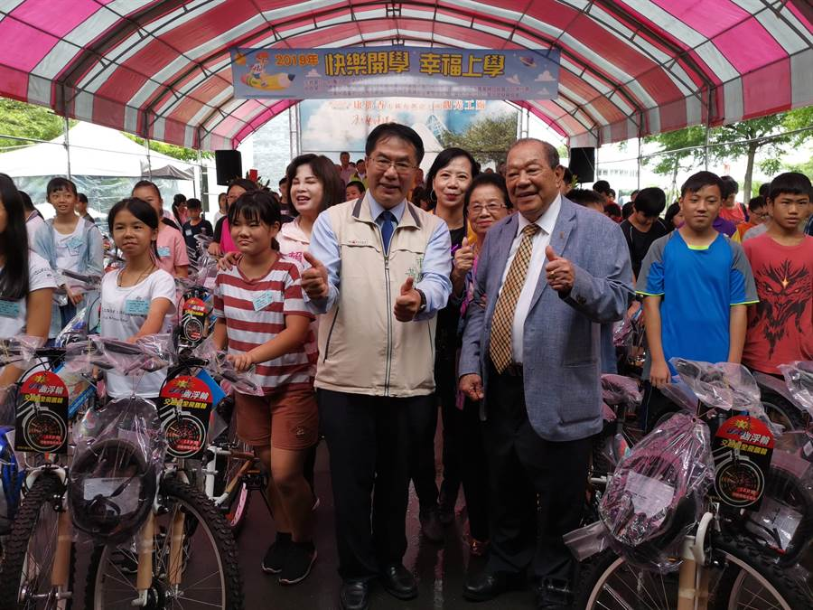 康那香董事長戴榮吉(前排右)以父親名義成立戴竹基金會,連續12年送百輛腳踏車及助學金給家扶兒童。(劉秀芬攝)