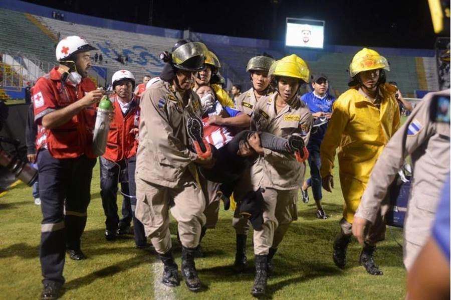 宏都拉斯足球賽前爆發球迷衝突,造成3死悲劇,為弭平這場足球暴動,當局出動大批警力,並施放催淚瓦斯。一名婦女被救援人員帶出球場。(路透)