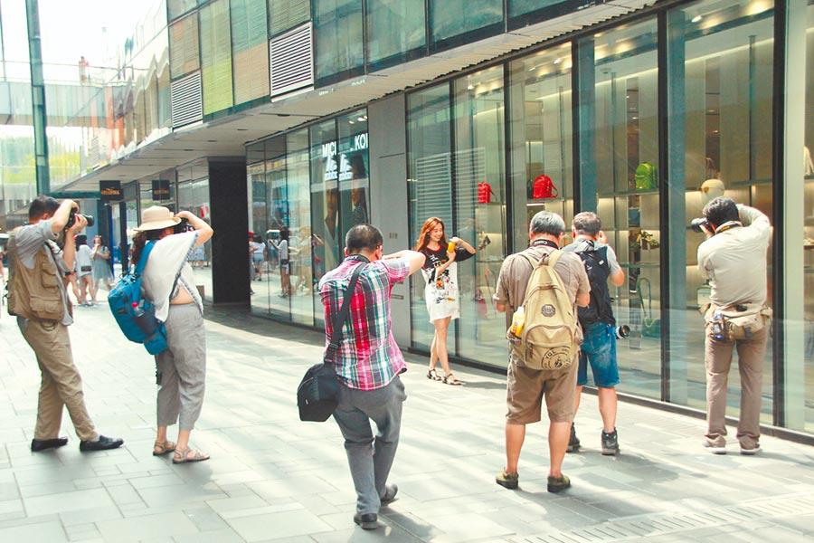 今昔對比。圖為2018年7月15日,年輕女性在北京三里屯逛街購物,招來攝影師搶拍。(中新社)