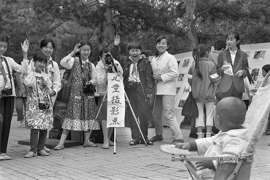 今昔對比。圖為1991年5月29日,北京日壇公園舉行兒童節遊園會,為小朋友拍照。(新華社)