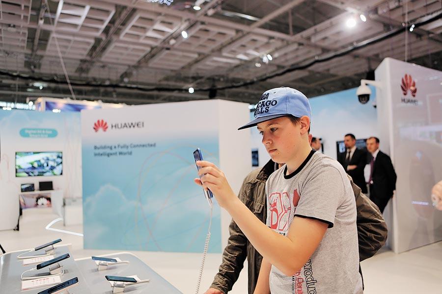 華為將在俄羅斯招募更多員工及研發專家。圖為2018年5月,在白俄羅斯國際通信和信息技術展上,一名年輕人體驗華為手機。(新華社)
