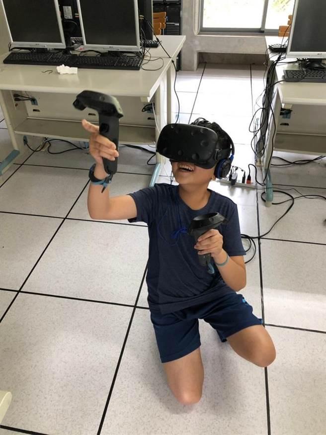 參加AI營的小朋友實地體驗VR虛擬實境的應用。(張穎齊翻攝)