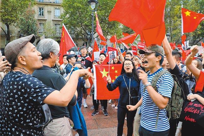 不少支持北京的僑胞帶著五星旗走上巴黎街頭,與支持反送中的民眾相互叫罵。(法新社)