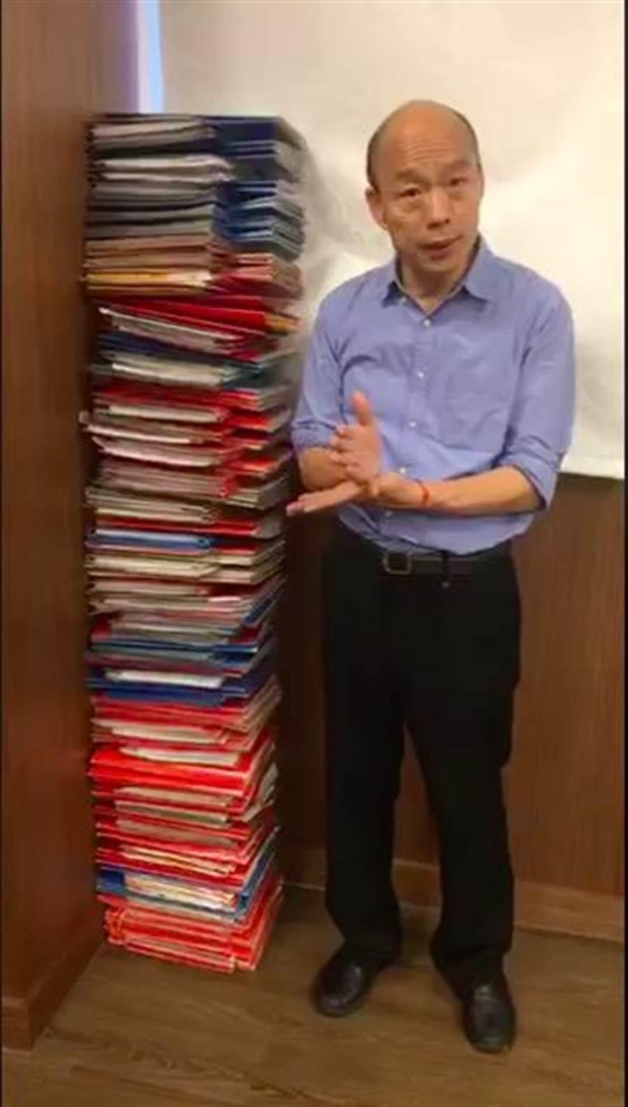 高雄市長韓國瑜中午開直播,堆出1人高的公文和行政院長蘇貞昌PK,呼籲民眾思考什麼樣的狀態才是更好的行政效率。(翻攝自韓國瑜臉書)