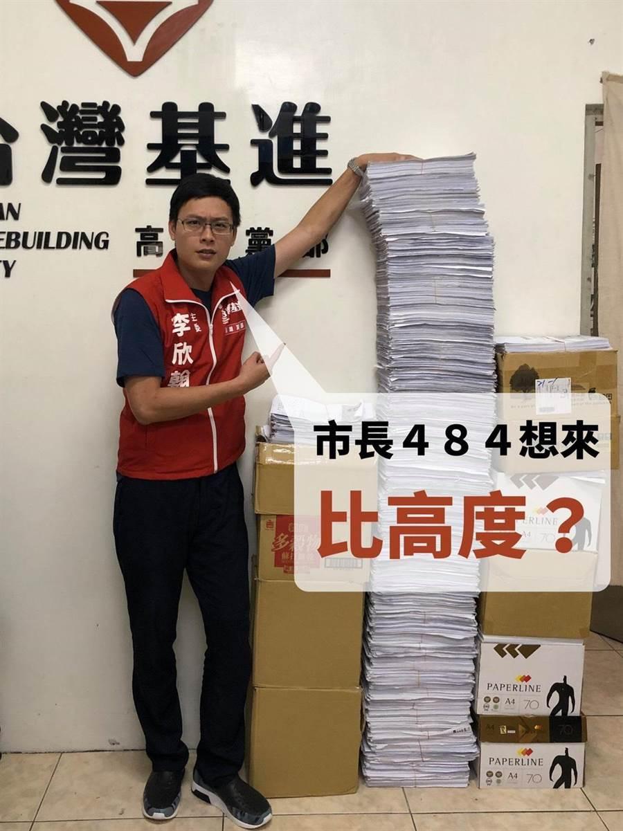 台灣基進高雄黨部主委李欣翰站在比自己還要高的罷免連署書旁,強調公文疊的越高、在位者越不認真。(袁庭堯翻攝)